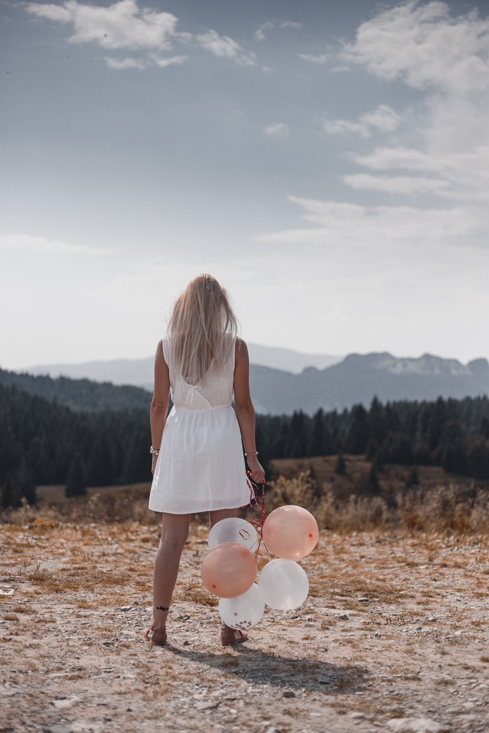 woman in white dress holding balloons