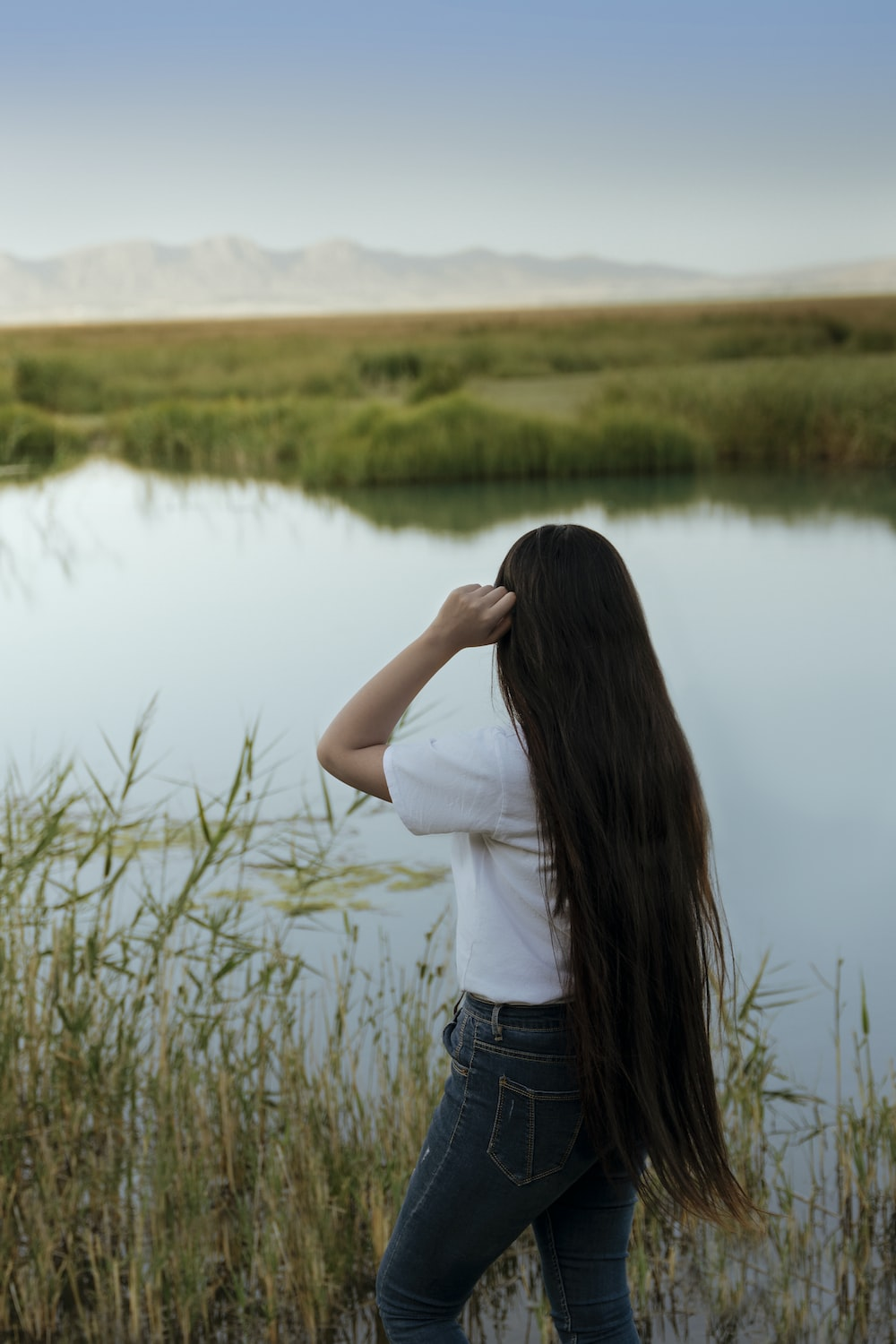 woman in white shirt and blue denim jeans standing near lake during daytime