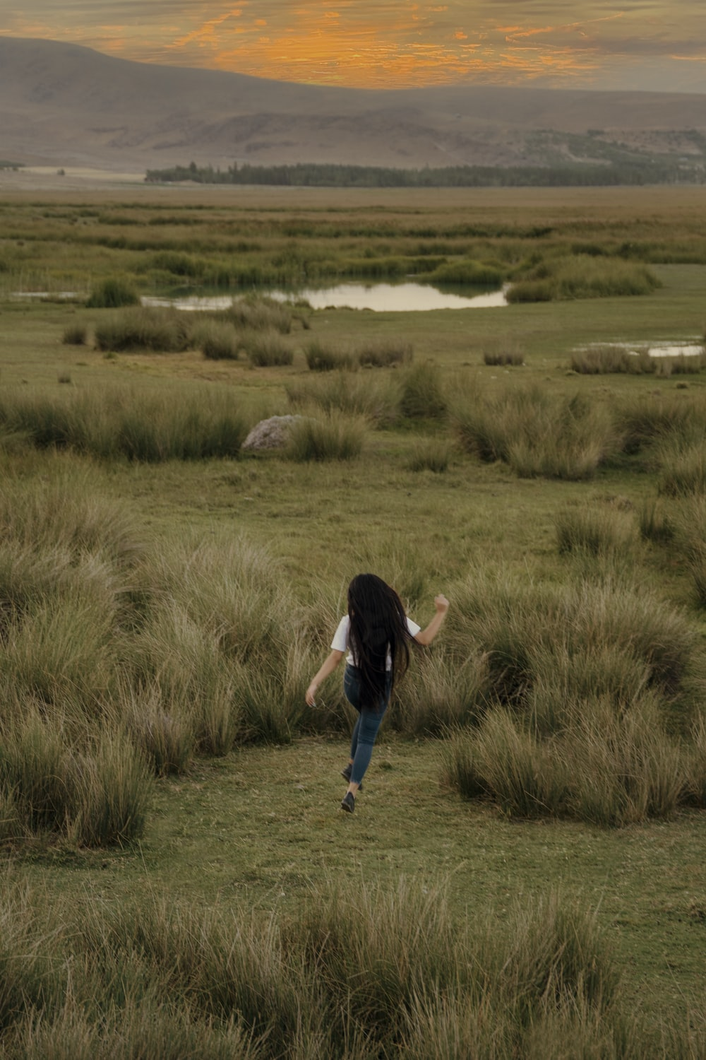 woman in black shirt and blue denim jeans walking on green grass field during daytime