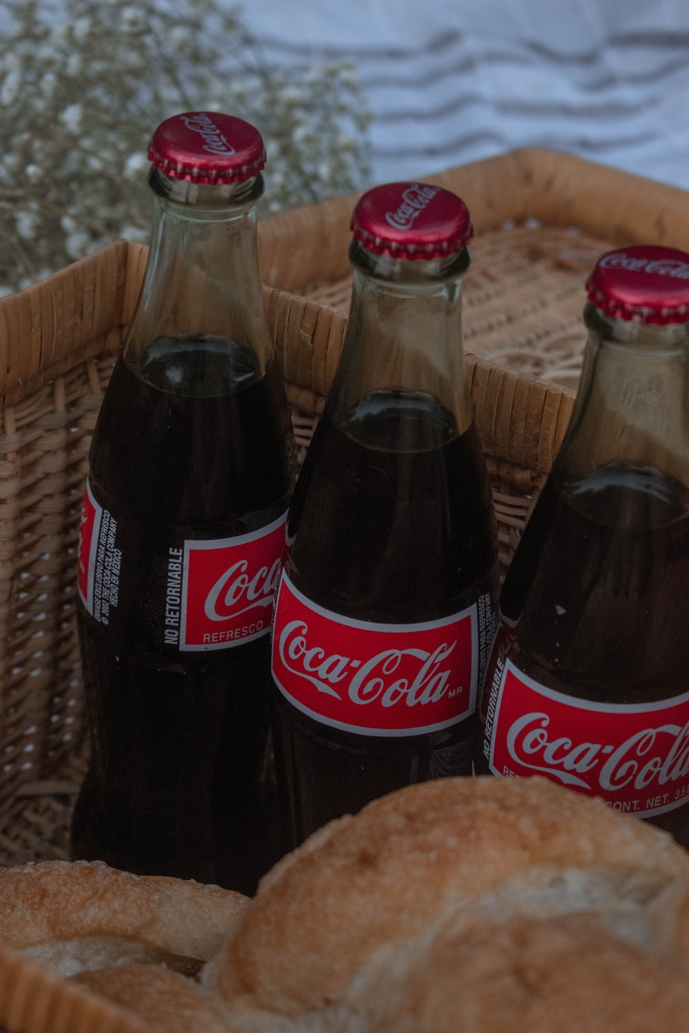 2 coca cola bottles on brown woven table