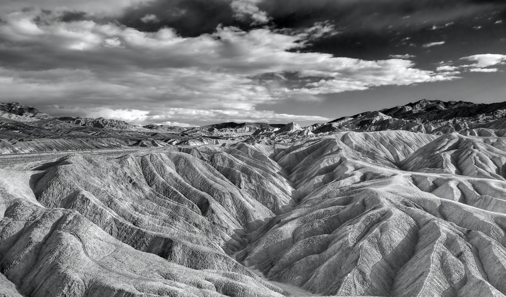 grayscale photo of rocky mountain under cloudy sky