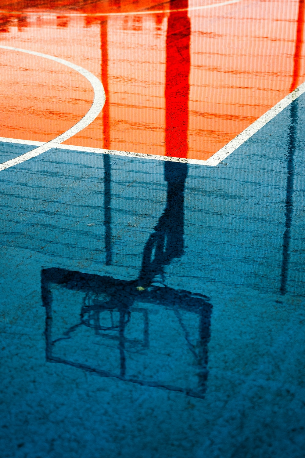 shadow of person on basketball court during daytime