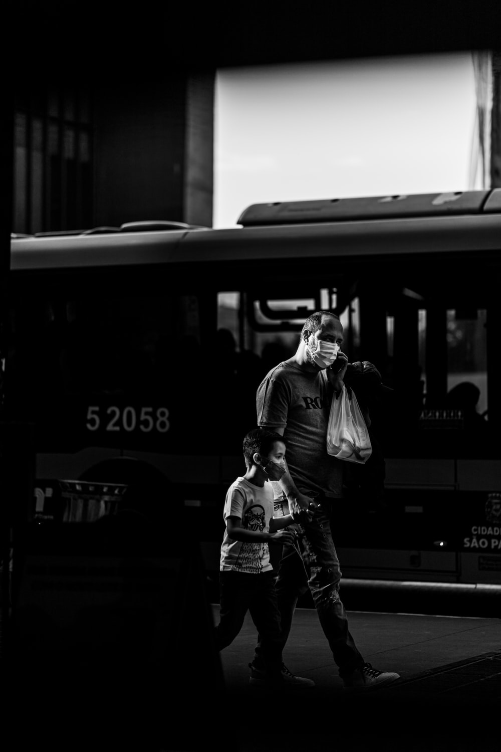 grayscale photo of woman in jacket and jeans standing beside train