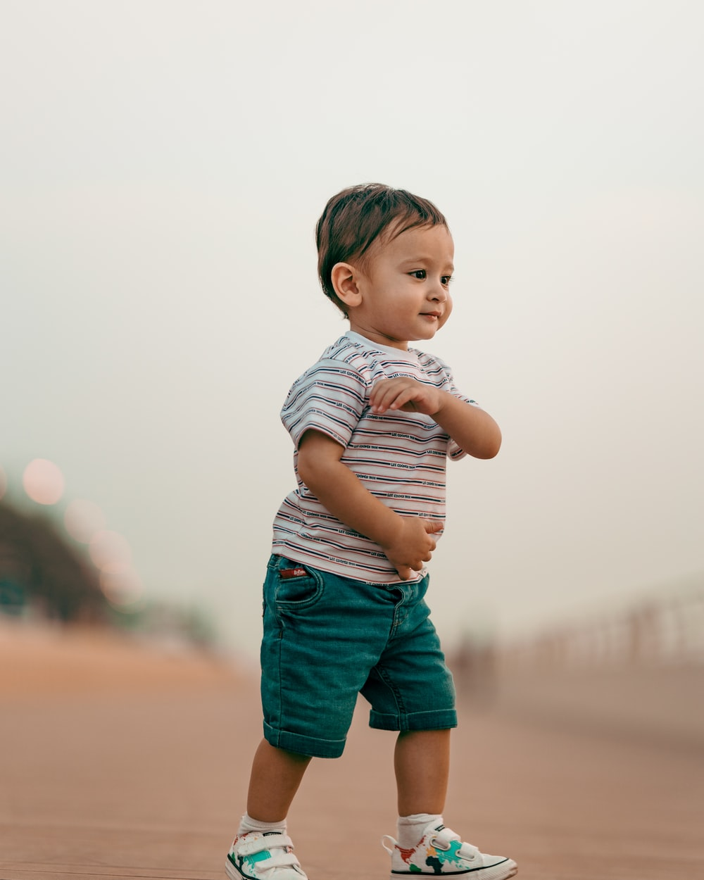 boy in white and black striped shirt and blue shorts standing on brown sand during daytime