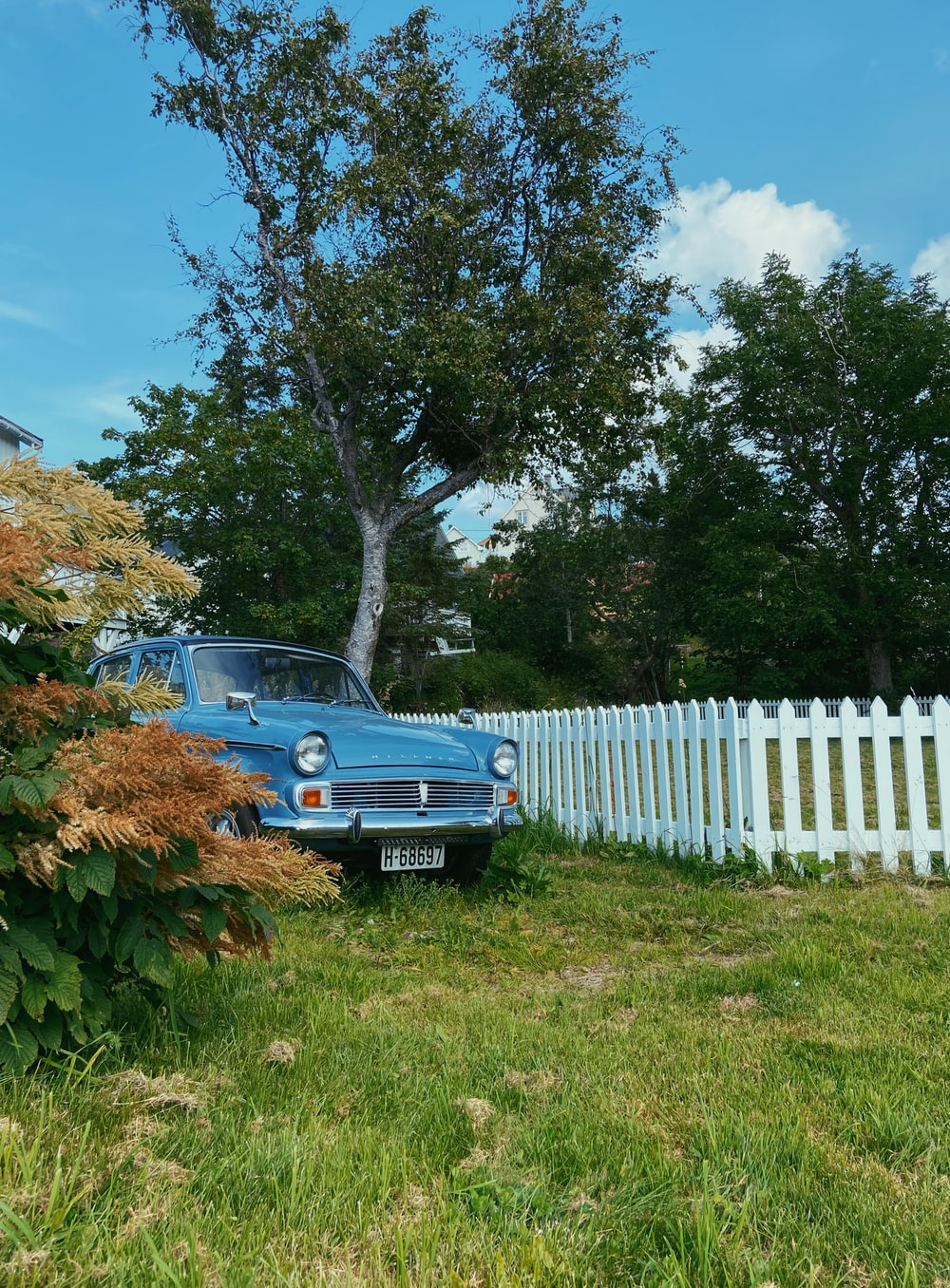 blue car parked beside white wooden fence during daytime