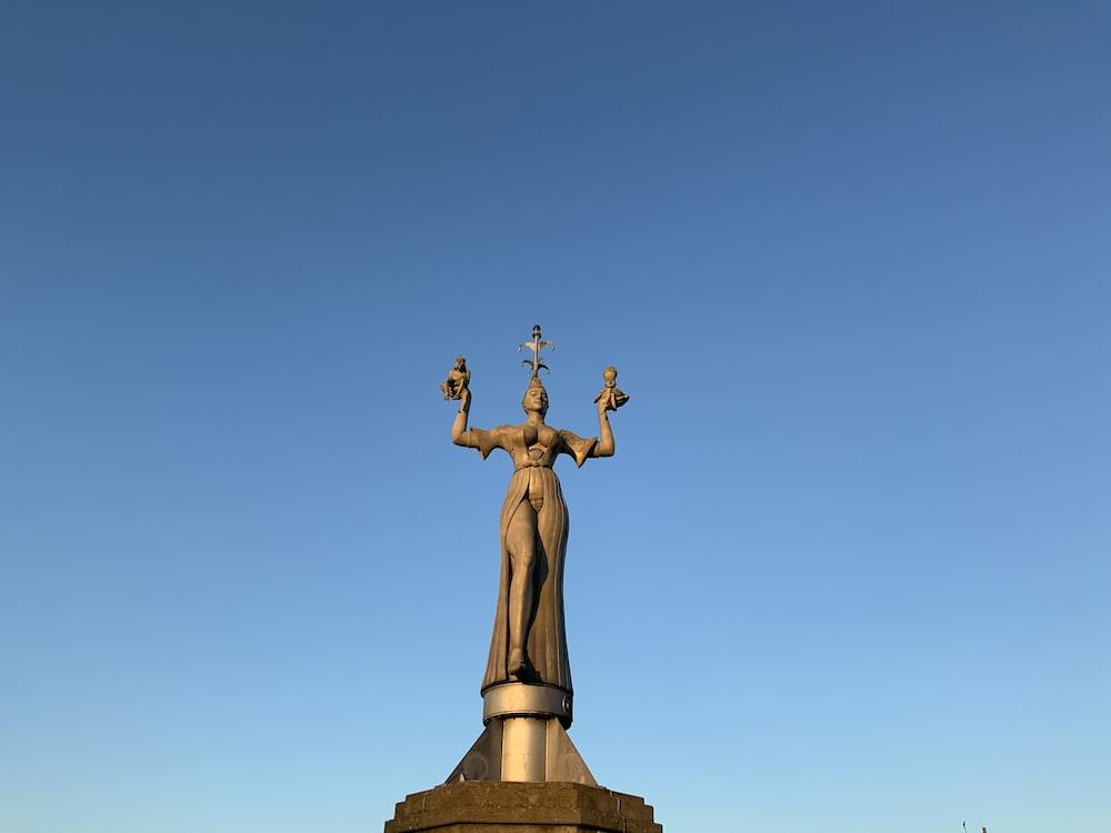 gold statue of man raising his hands