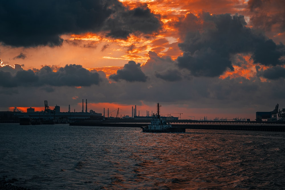 silhouette of ship on sea under cloudy sky during sunset