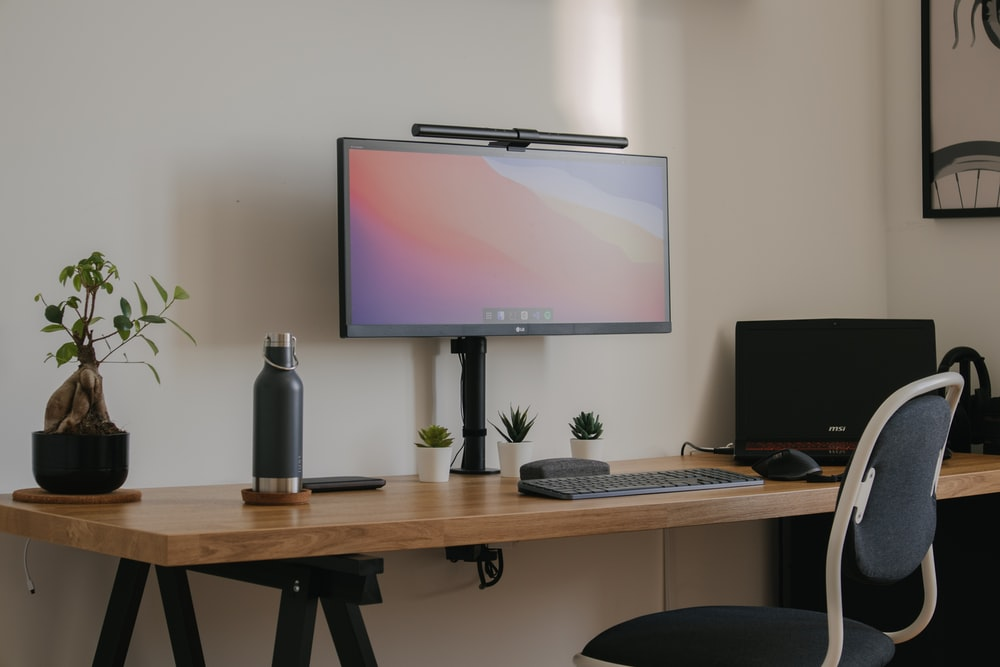 black flat screen tv turned on near black computer keyboard on brown wooden table