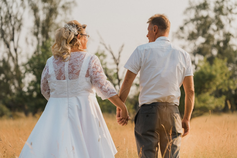 man in white shirt and woman in white dress