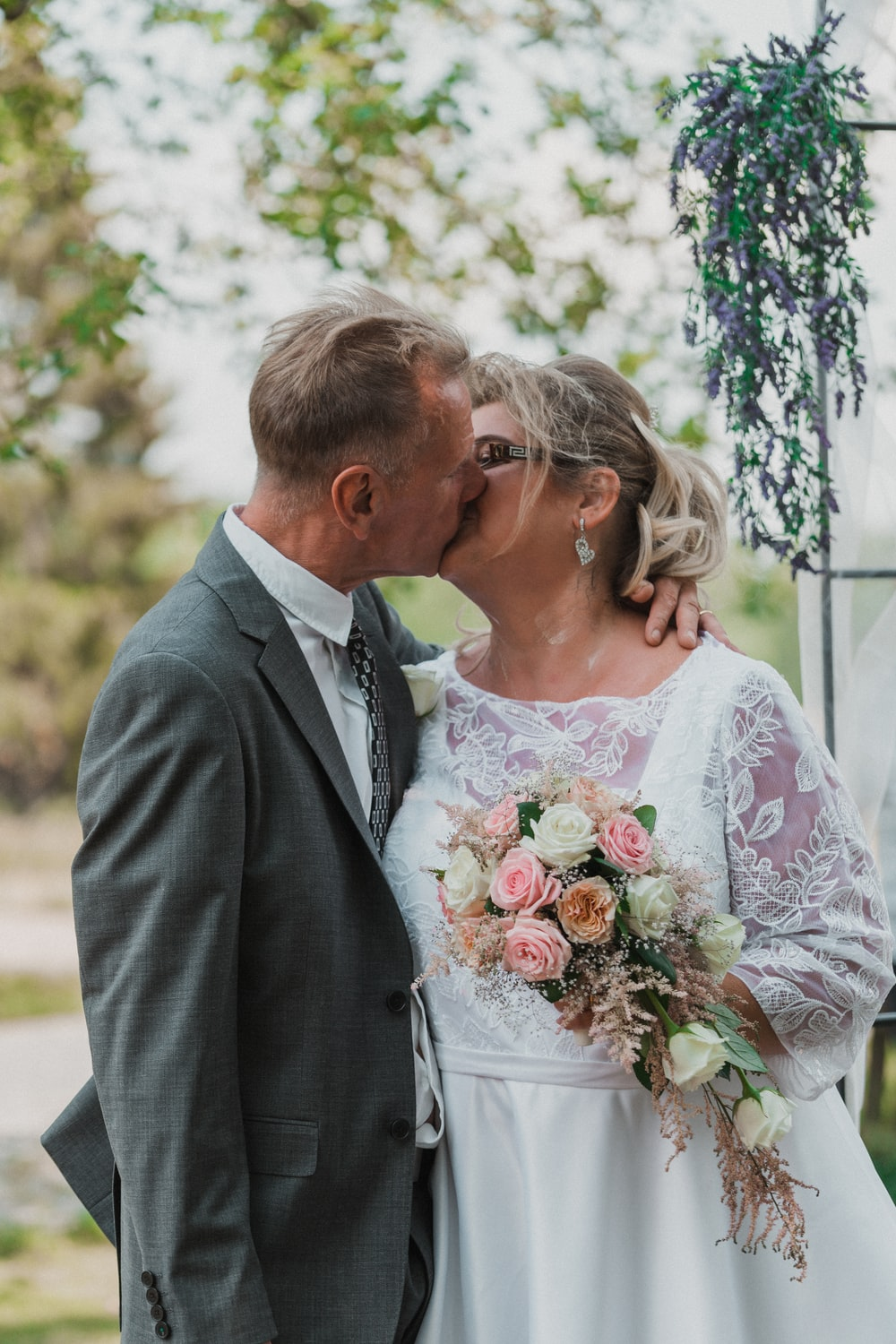 man in black suit kissing woman in white floral dress