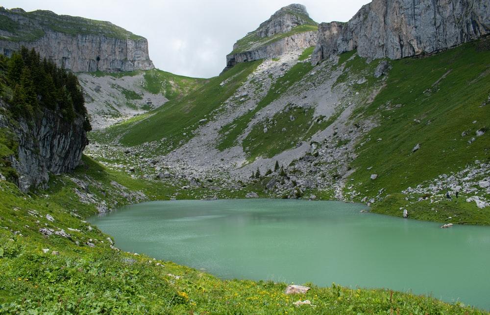 green lake between gray rocky mountains during daytime