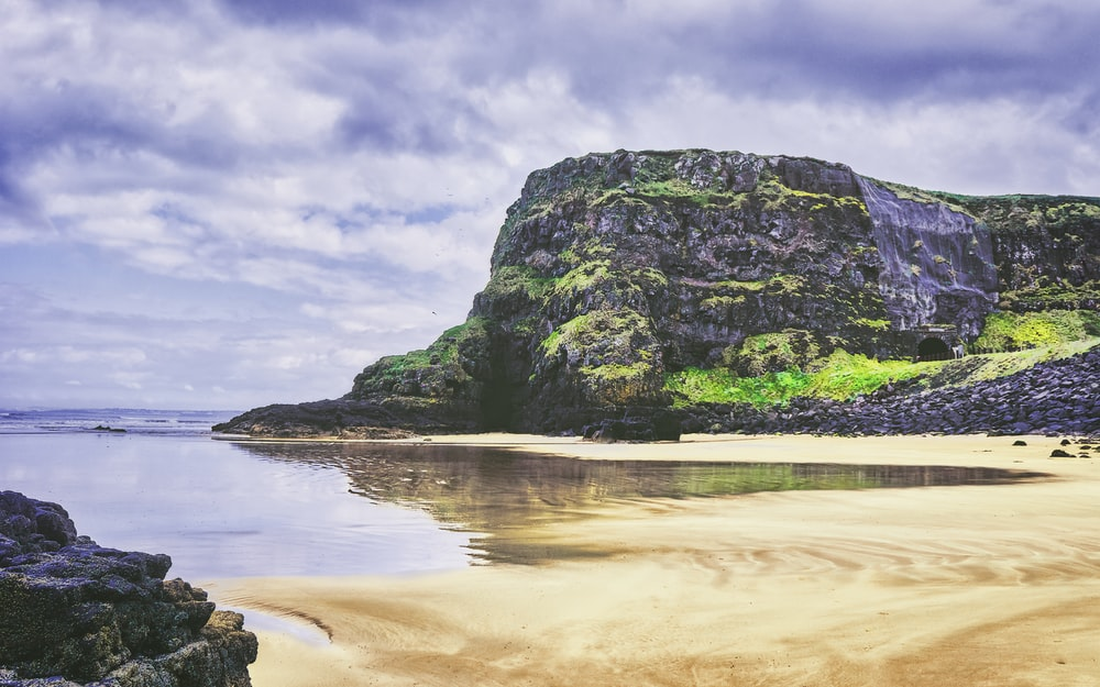 green and brown rock formation on sea shore under white clouds and blue sky during daytime