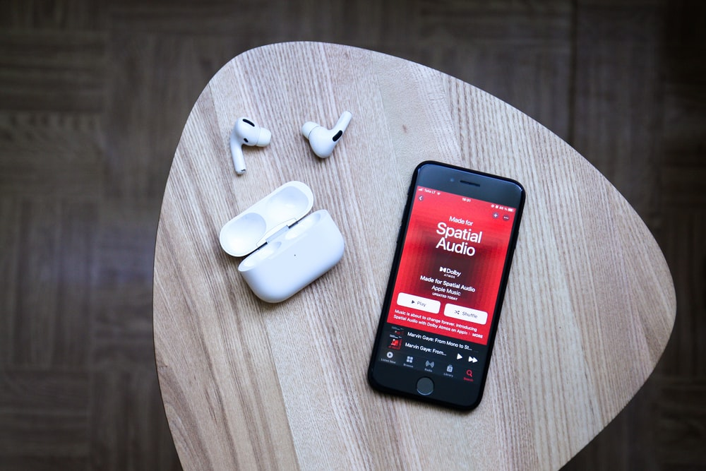 black android smartphone beside white earbuds on brown wooden table