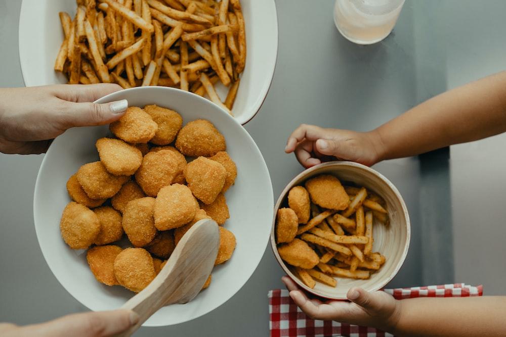 brown potato fries on white ceramic bowl