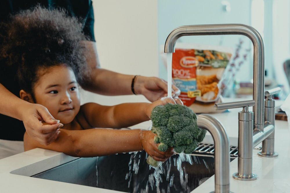 girl holding green kush on stainless steel sink