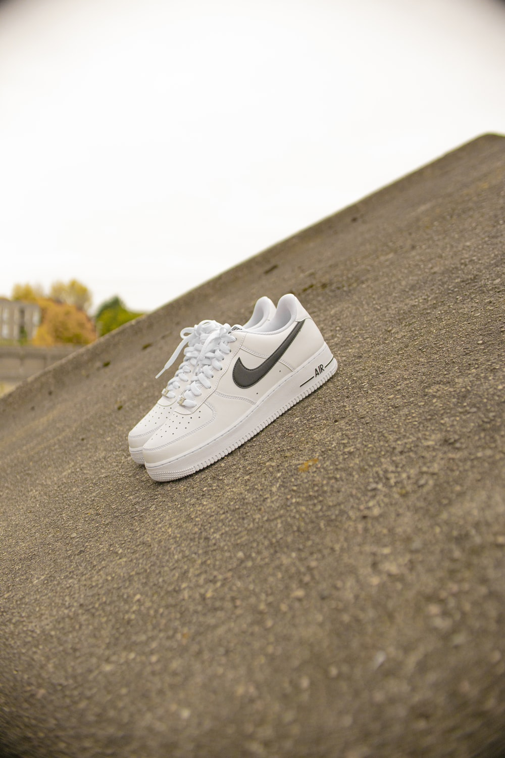 white nike air force 1 low on gray asphalt road during daytime