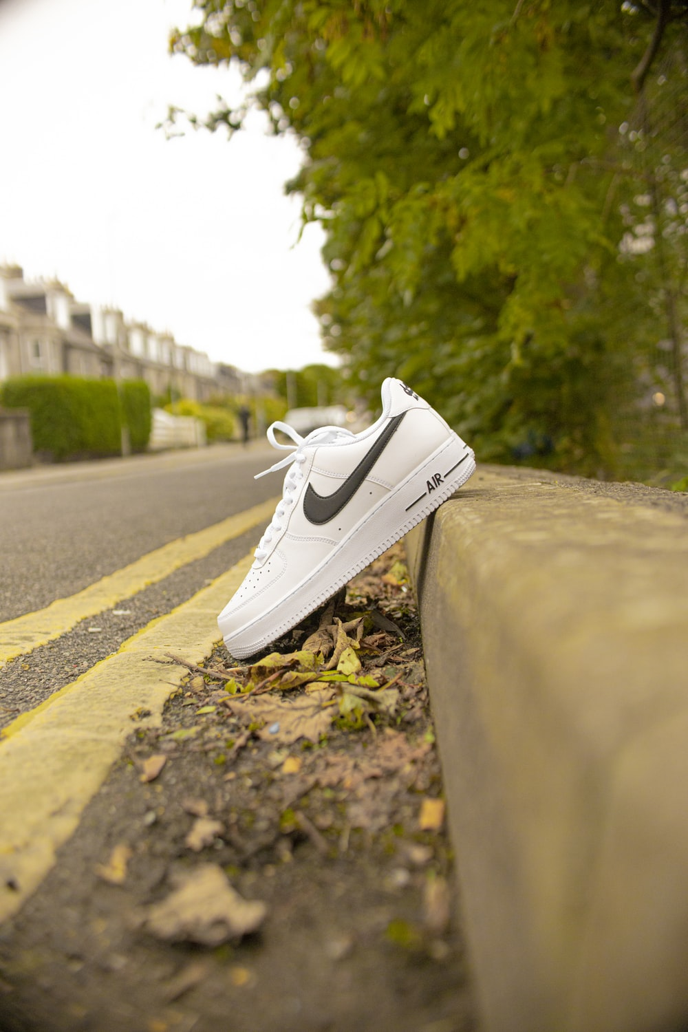 white nike low top sneakers on gray concrete road