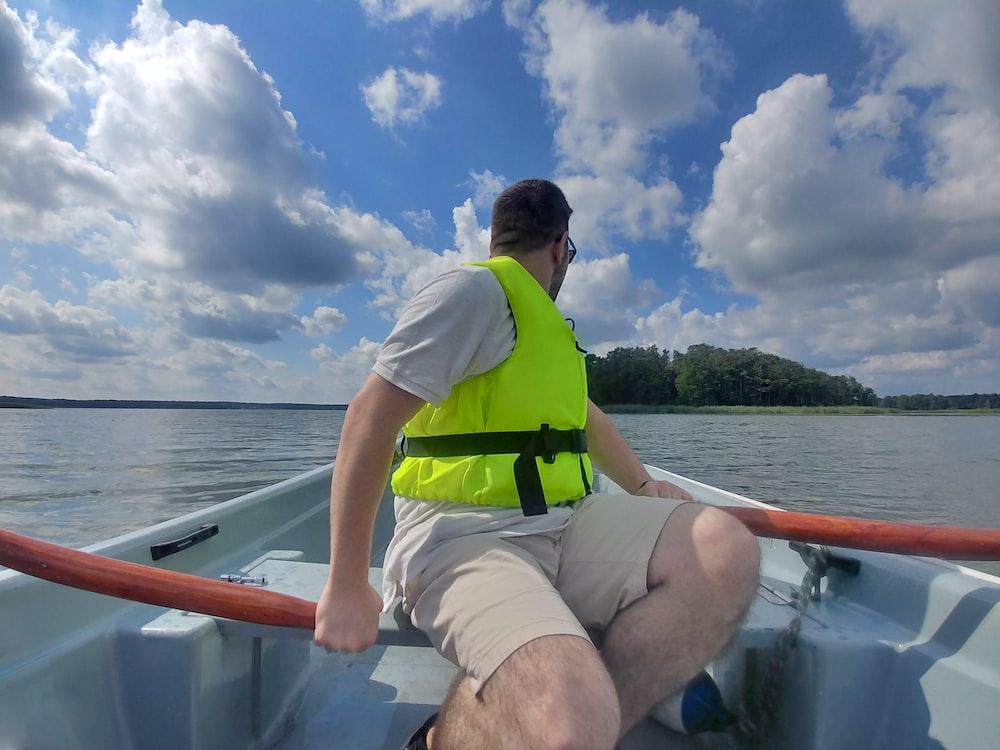 man in green shirt sitting on boat during daytime