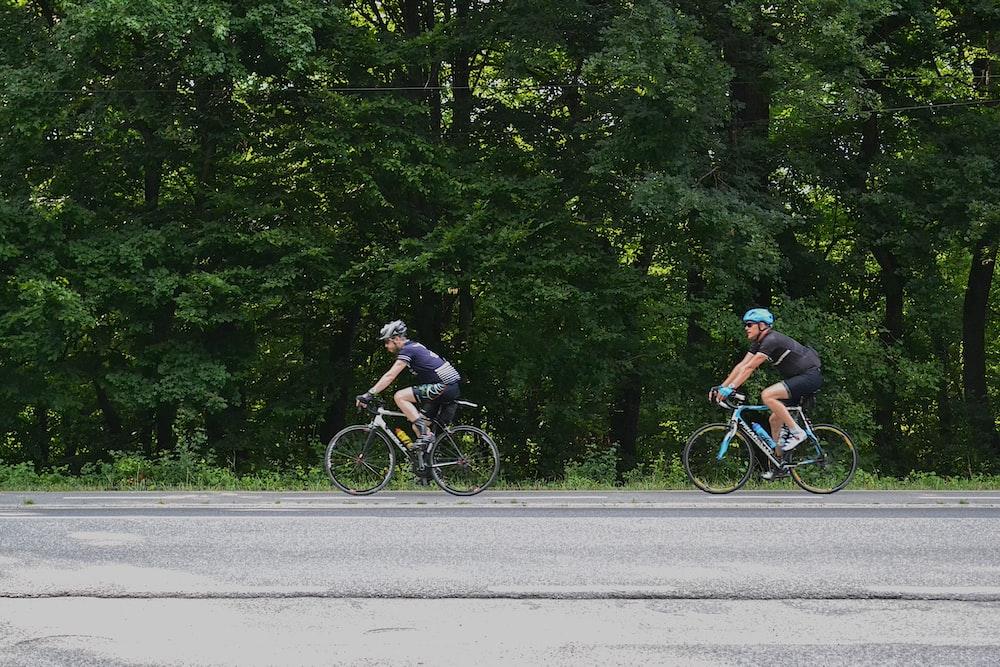 2 men riding bicycle on road during daytime