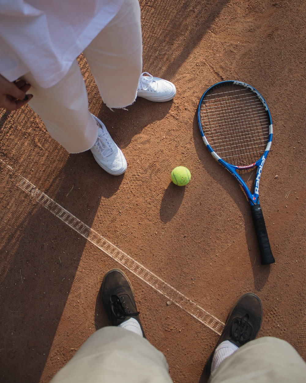 person in white pants and black shoes standing beside tennis racket