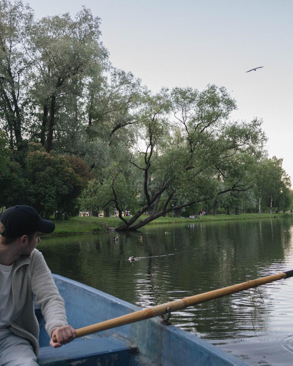 man in white shirt sitting on boat during daytime