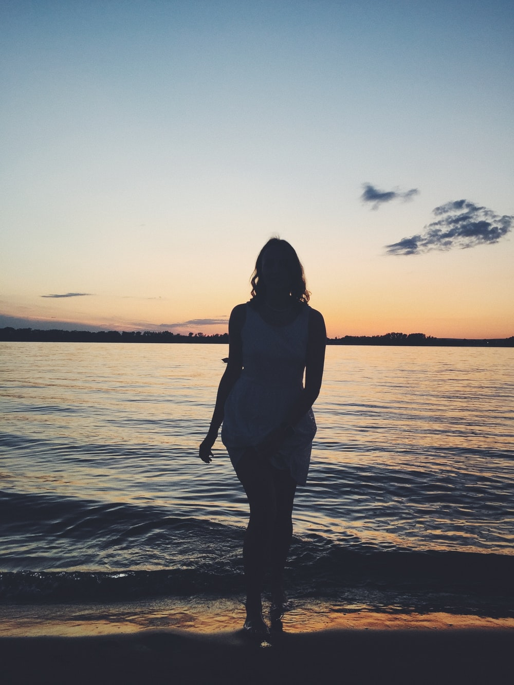 woman in black tank top standing on beach during sunset