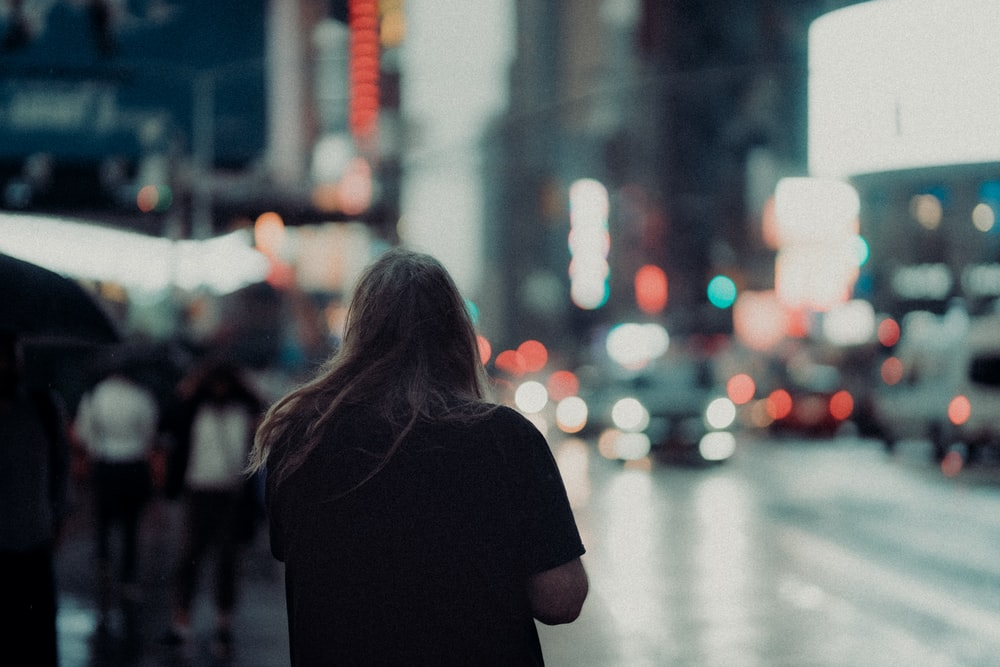 woman in black shirt standing on street during daytime