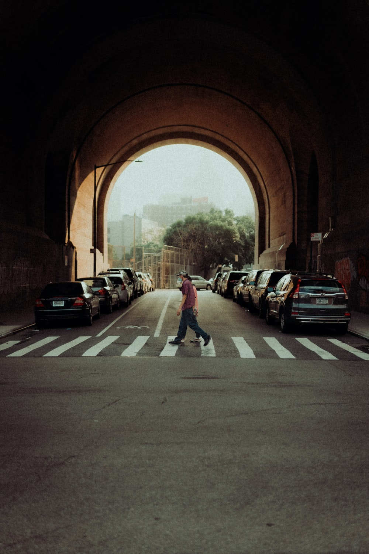 man in blue denim jeans walking on sidewalk during daytime