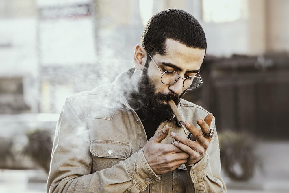 man in brown jacket smoking cigarette