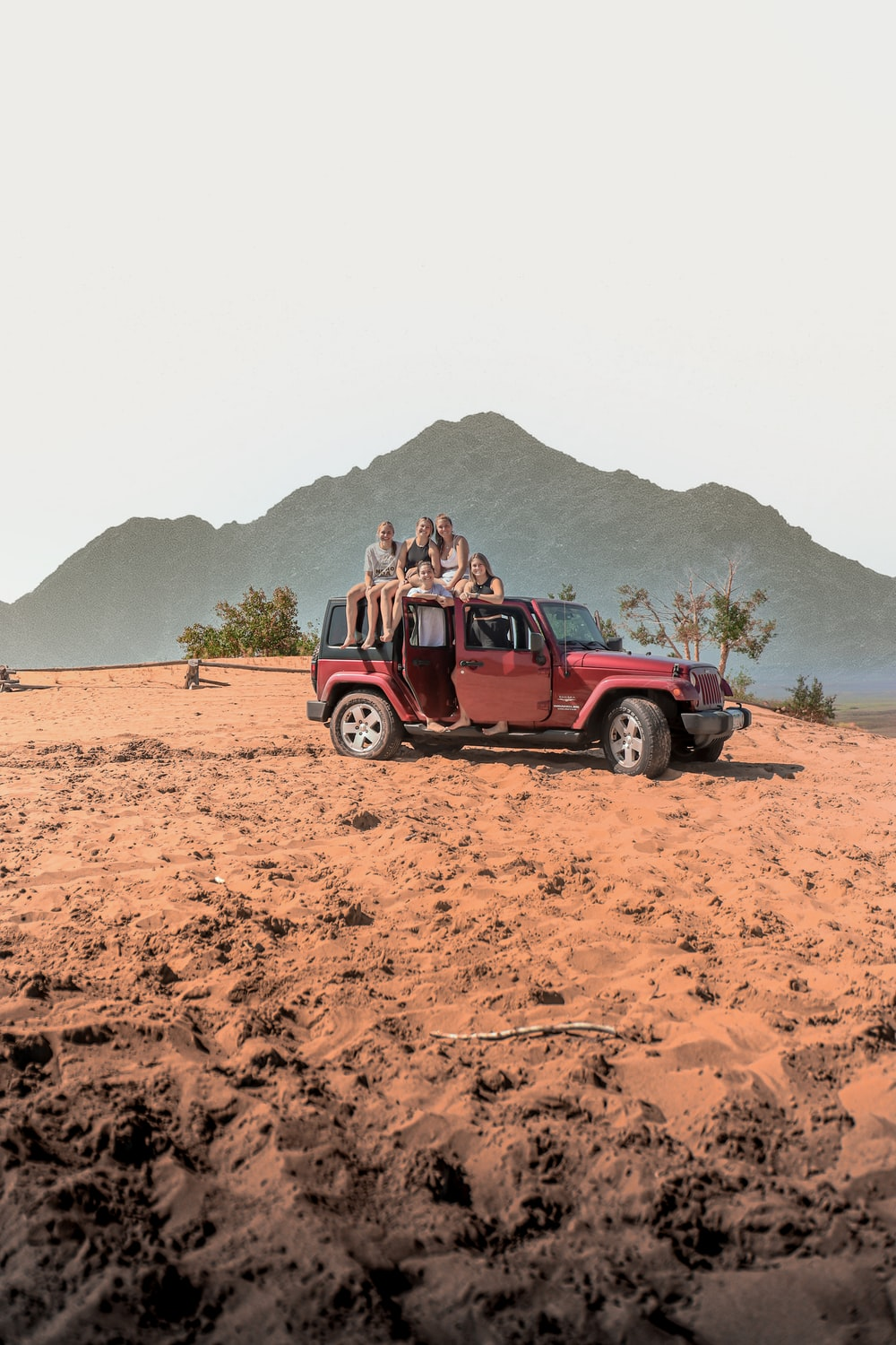 red suv on brown sand during daytime