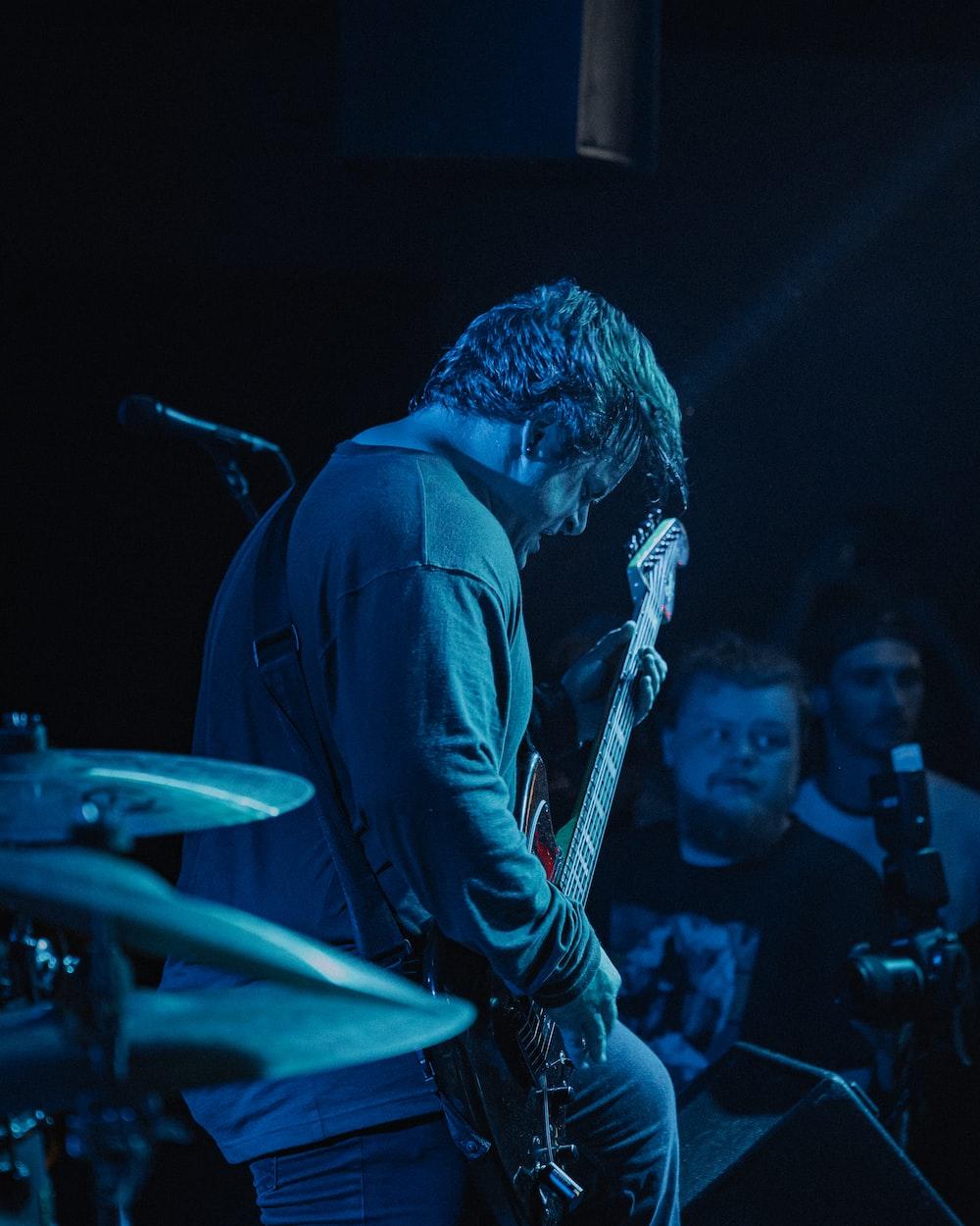 man in black shirt playing guitar