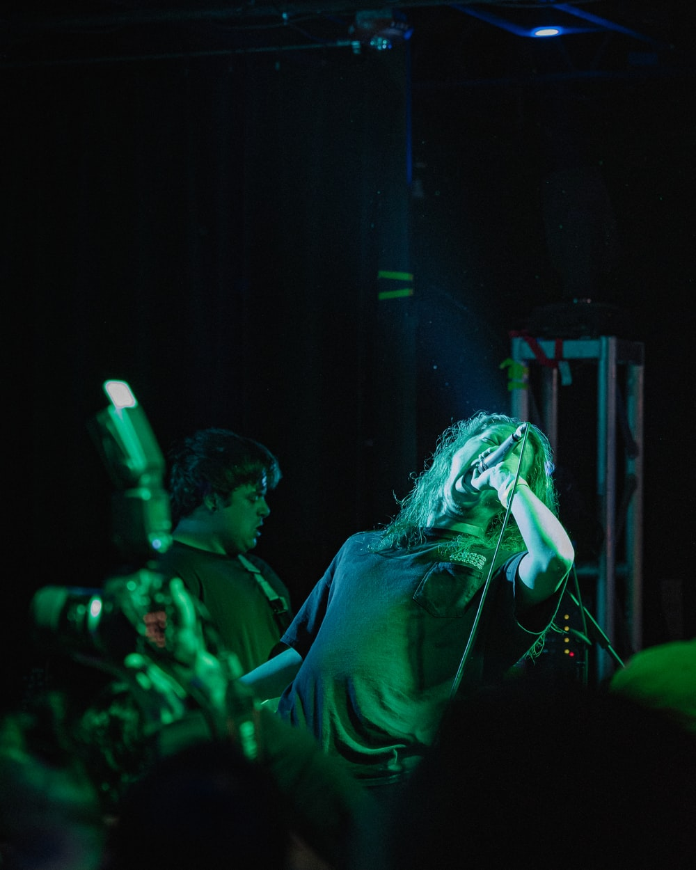 woman singing on stage in front of people