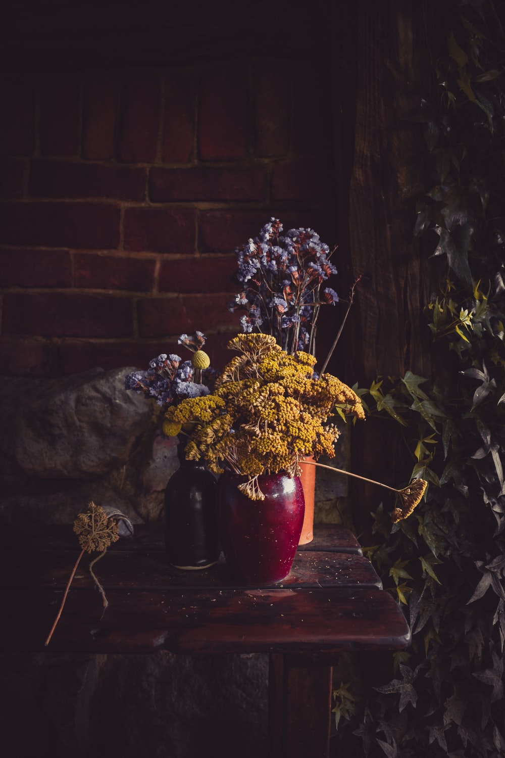white and yellow flowers in red ceramic vase