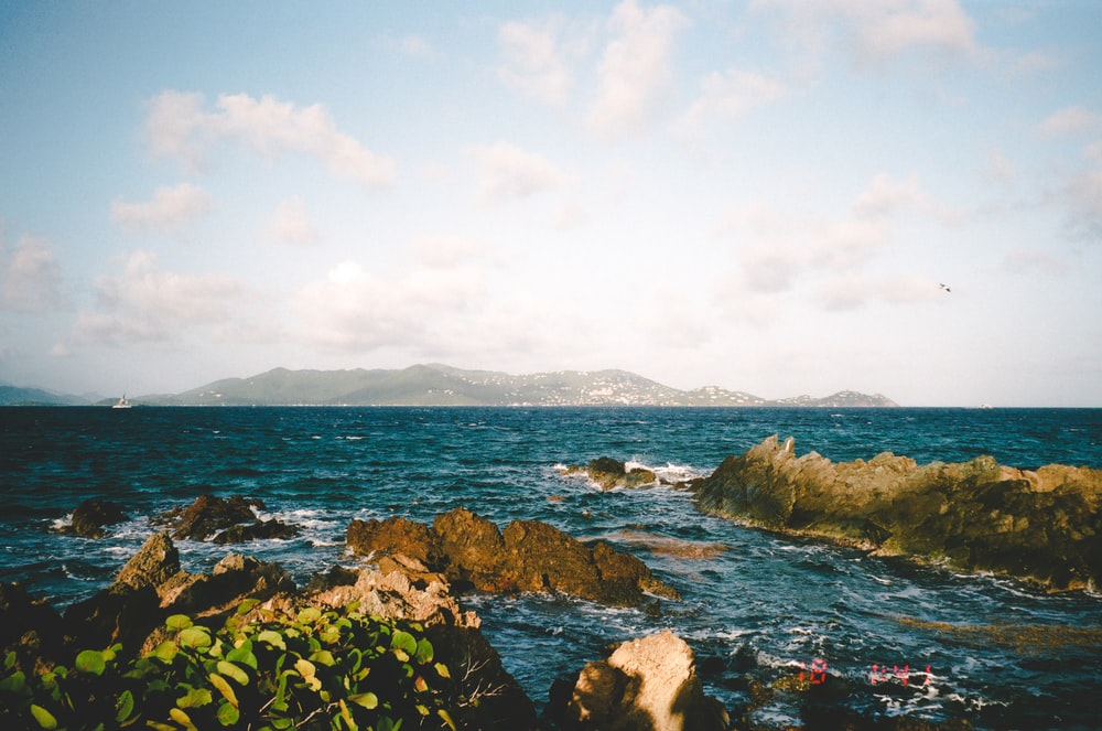 rocky shore with green moss and blue sea water under white clouds and blue sky during