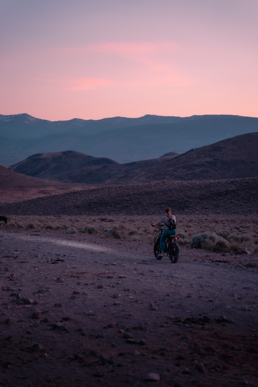 man in red jacket riding motorcycle on dirt road during daytime