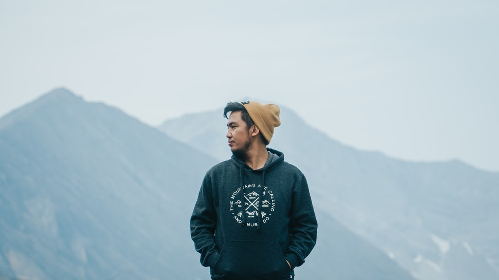 man in black and white sweater standing on top of mountain during daytime