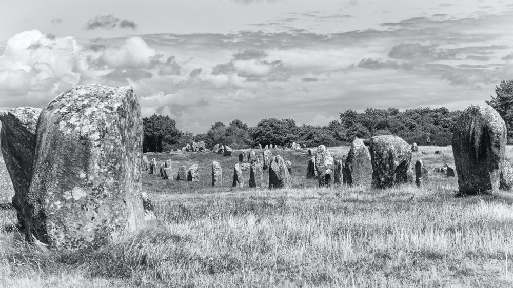 grayscale photo of rock formation on grass field