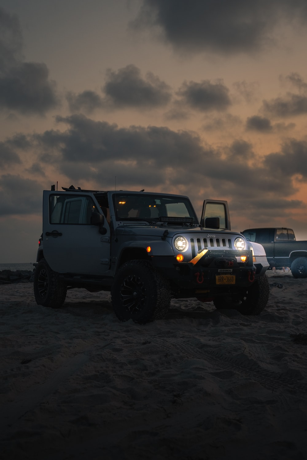 blue jeep wrangler on brown field under gray cloudy sky during daytime