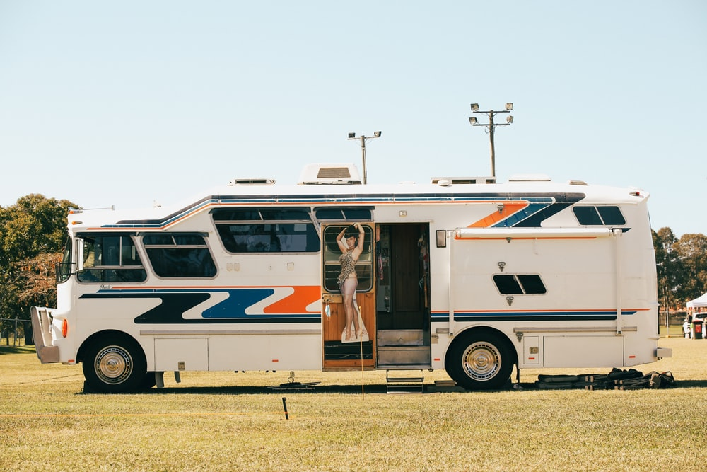 white and brown bus on green grass field during daytime