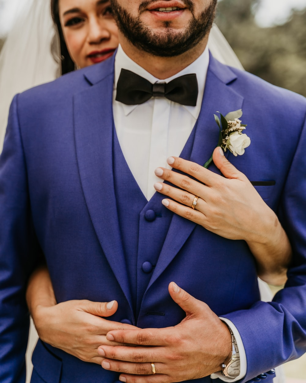 man in blue suit jacket holding white rose