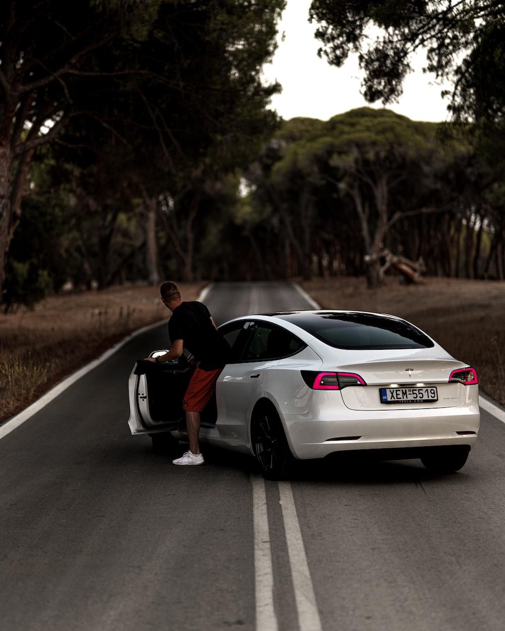 man in black t-shirt sitting on white sedan on road during daytime