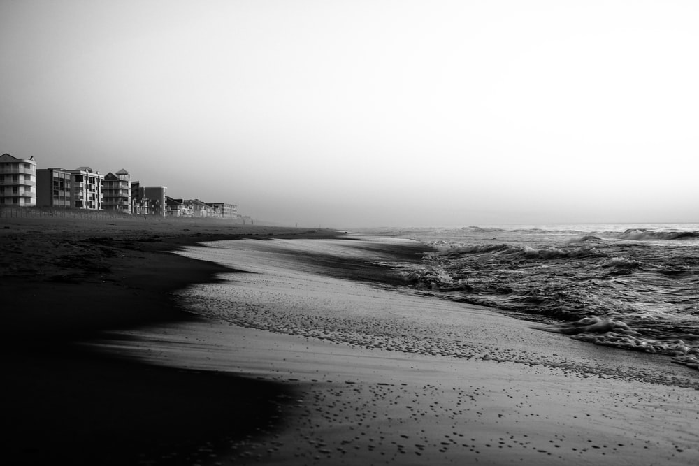 grayscale photo of beach and buildings