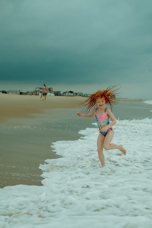 woman in white bikini walking on white sand beach during daytime