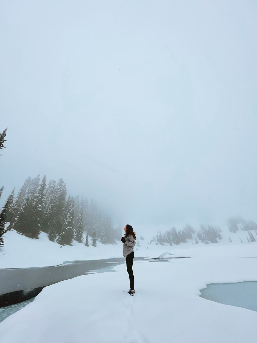 woman in white jacket and black pants standing on snow covered ground during daytime