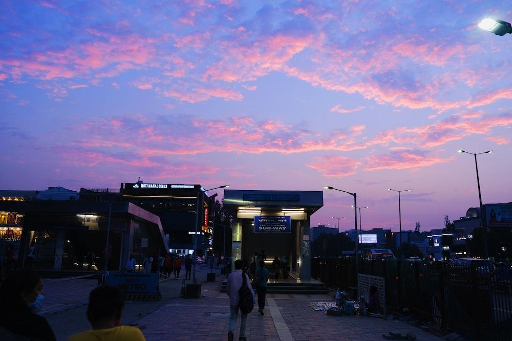 people walking on sidewalk near building during sunset