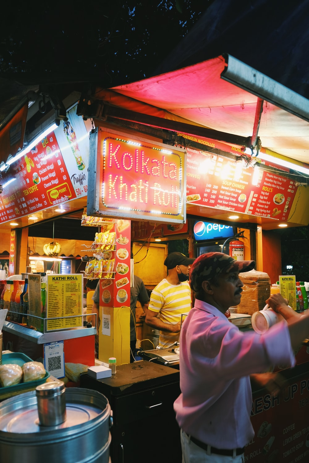 woman in pink shirt standing in front of food stall