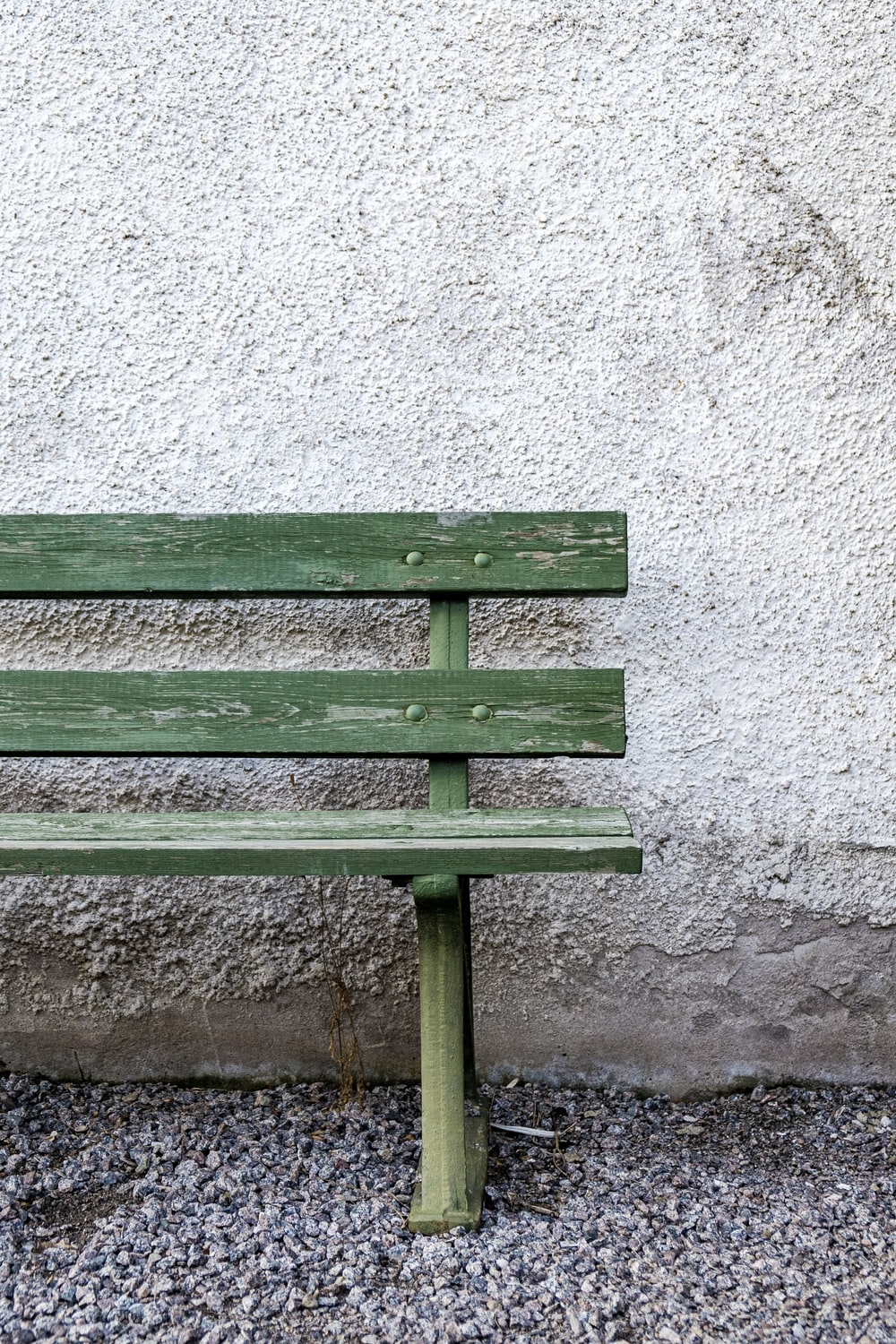 green wooden bench beside white wall