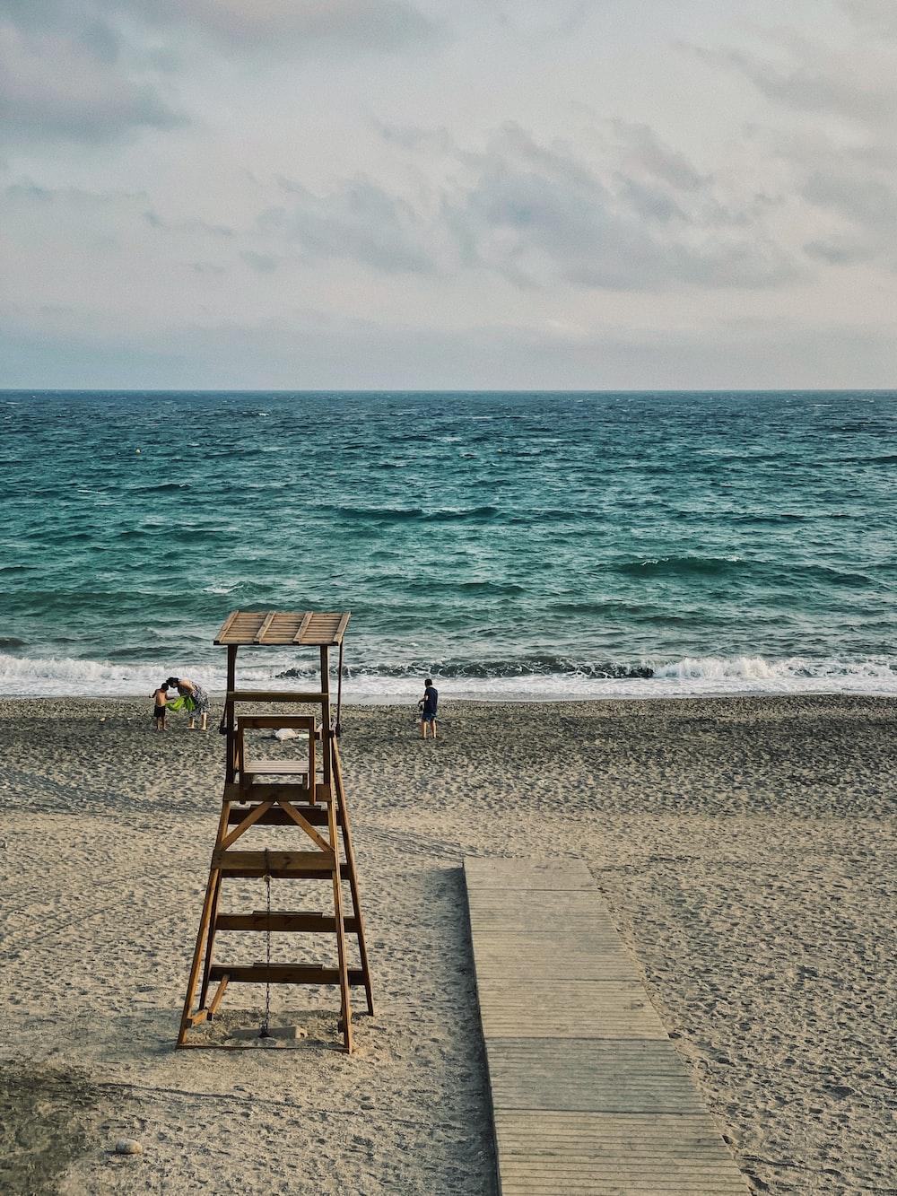 brown wooden beach chair on beach during daytime