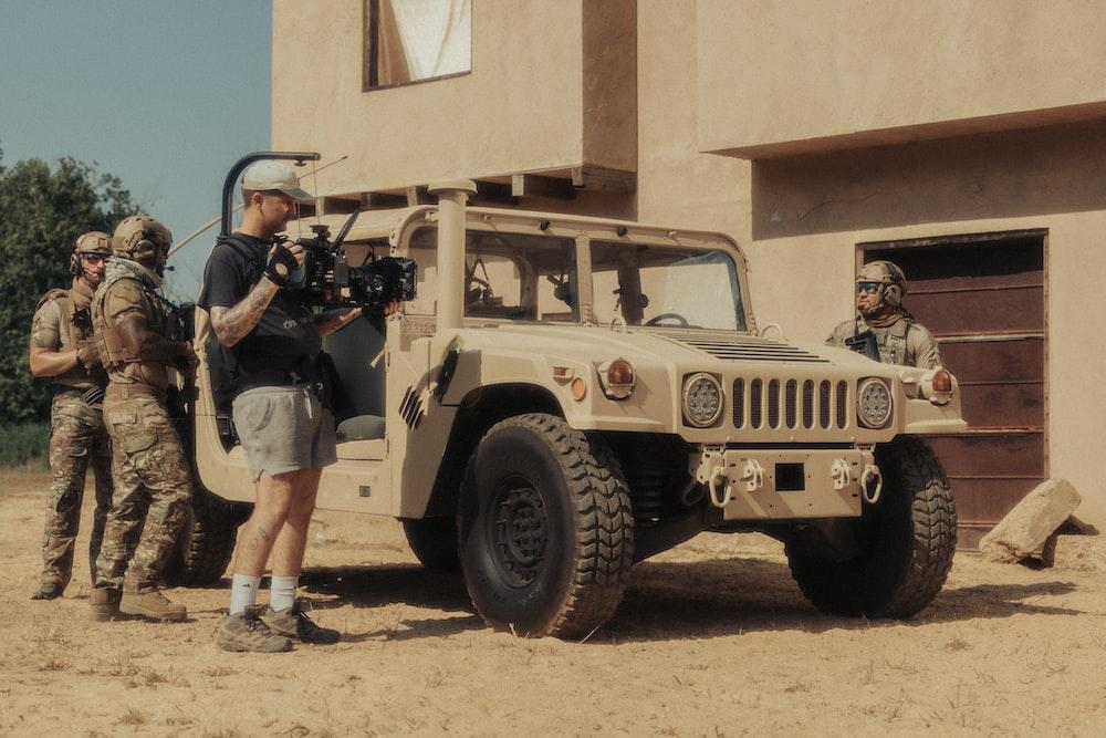 2 boys standing beside brown jeep wrangler