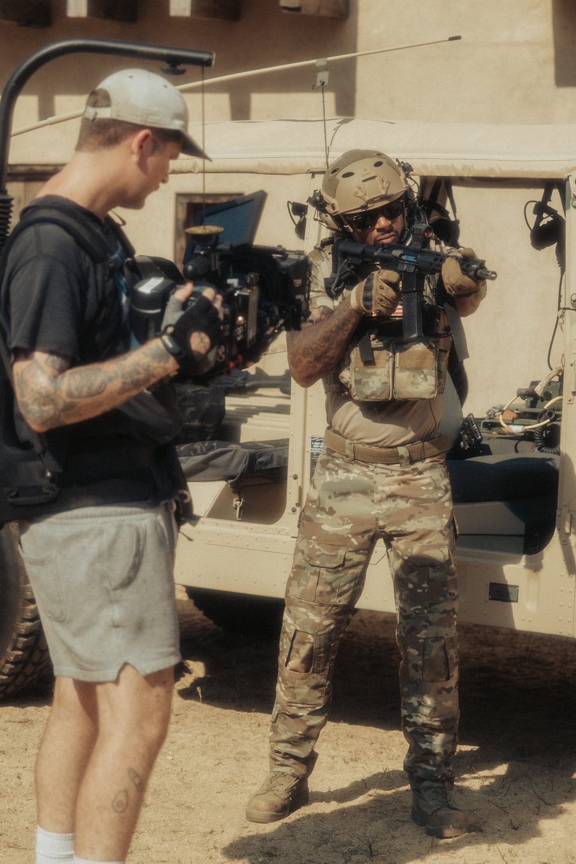 man in green camouflage uniform holding black dslr camera